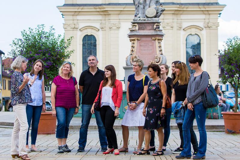 Eine Gruppe von Menschen steht vor dem Brunnen auf dem Marktplatz und schaut und hört gespannt einer Gästeführerin zu.