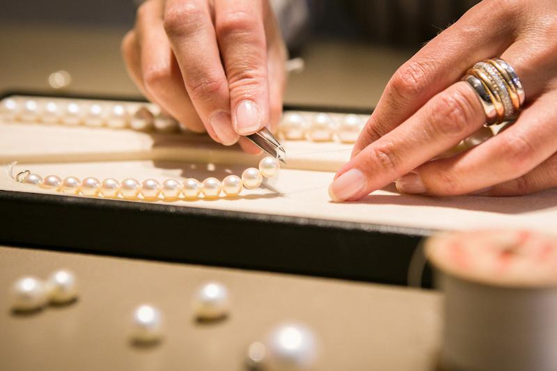 Nahaufnahme von zwei Händen, die eine Perlenkette knüpfen
