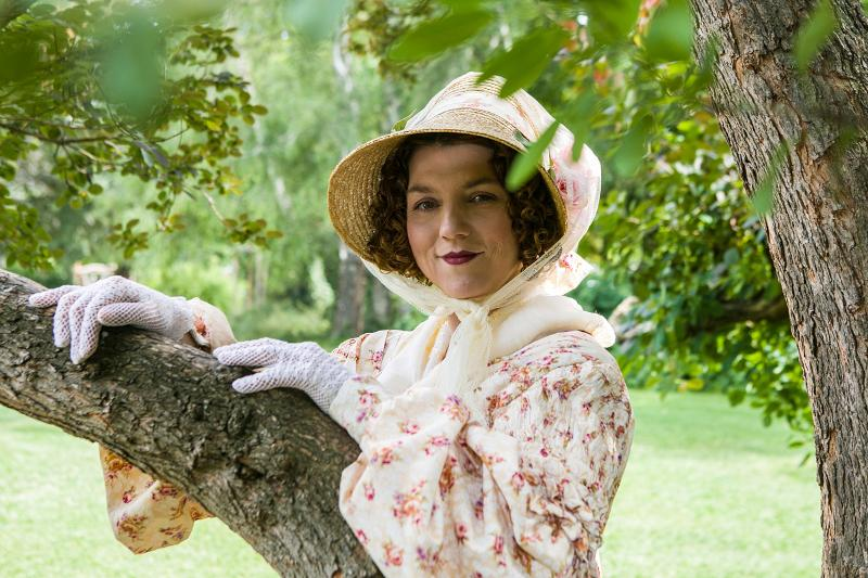 Eine Frau mit weißen Handschuhen, einem geblümten Hut und einem ebenfalls geblümten Kleid steht hinter einem Ast eines Baumes auf einer Wiese.