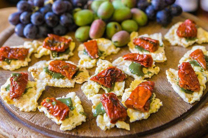 Auf einem Holzbrett liegen im Hintergrund helle und dunkle Trauben. Im Vordergrund liegen Häppchen mit eingelegten Tomaten und grünem Pesto.