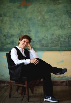 Die Autorin Ebru Nihan Celkan sitzt auf einem schwarzen Stuhl vor einer grünen Wand.
